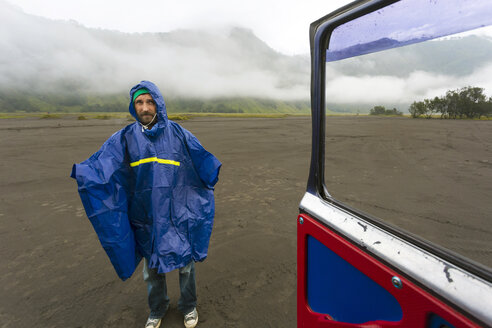 Man in rain coat with volcanic dust,Bromo,Java,Indonesia - AURF05311