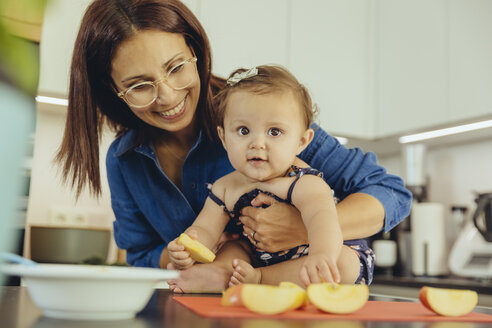 Mother and baby daughter eating apple chunks in kitchen - MFF04646