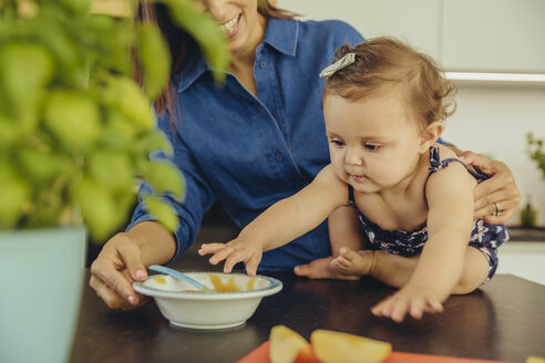 Mother with baby daughter eating fruit pulp in kitchen - MFF04649