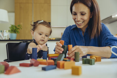 Happy mother and baby daughter playing with building blocks - MFF04655