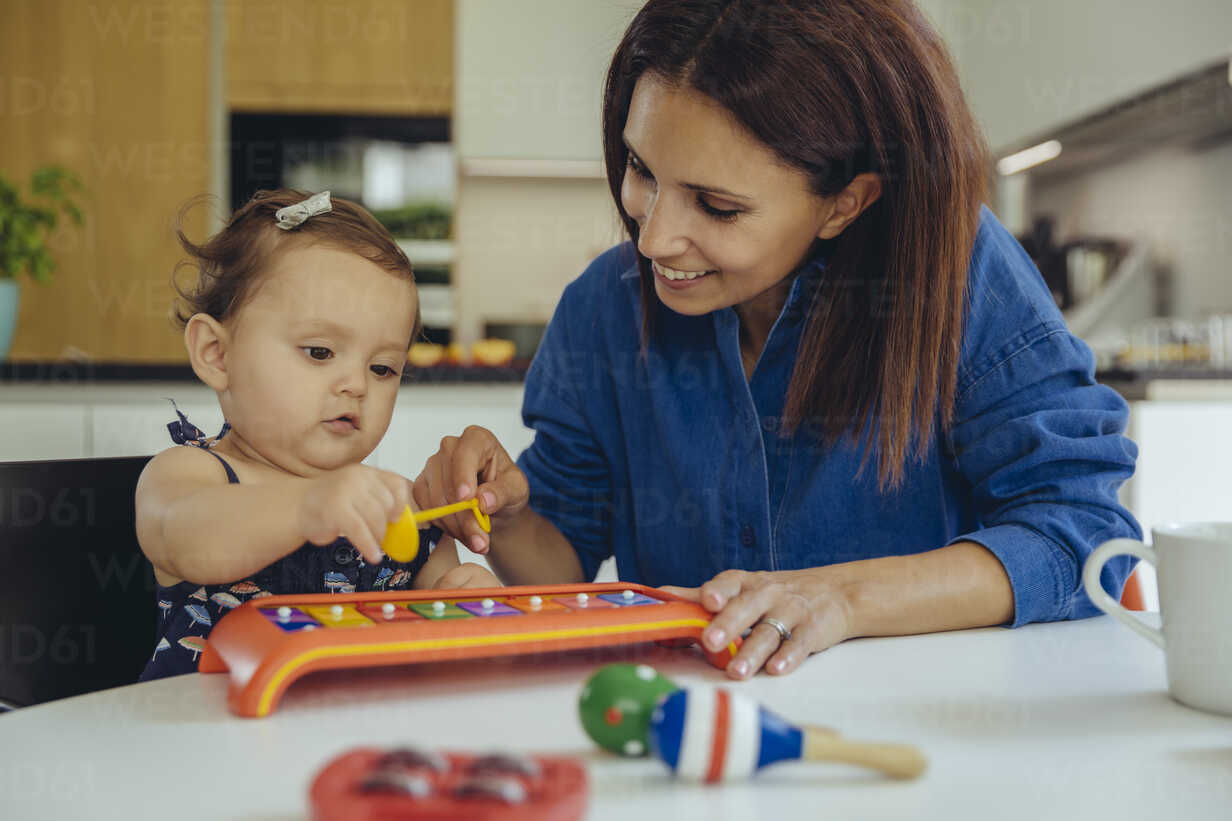 Happy mother and baby daughter playing with a glockenspiel - MFF04658 - Mareen Fischinger/Westend61
