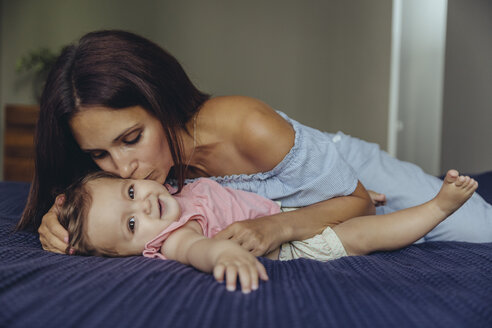 Mother kissing her baby girl on bed - MFF04661