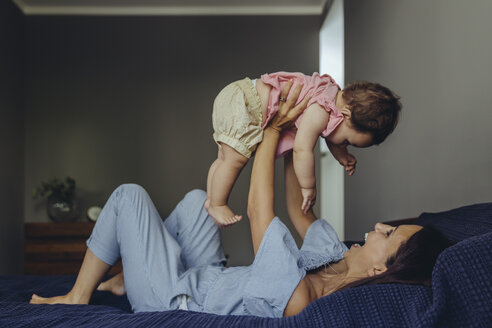 Happy mother lifting up her baby girl on bed - MFF04667