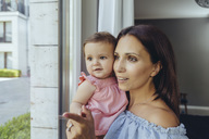 Smiling mother looking out of window with baby daughter at home - MFF04673