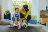 Happy mother with baby daughter on toy car in living room - MFF04676