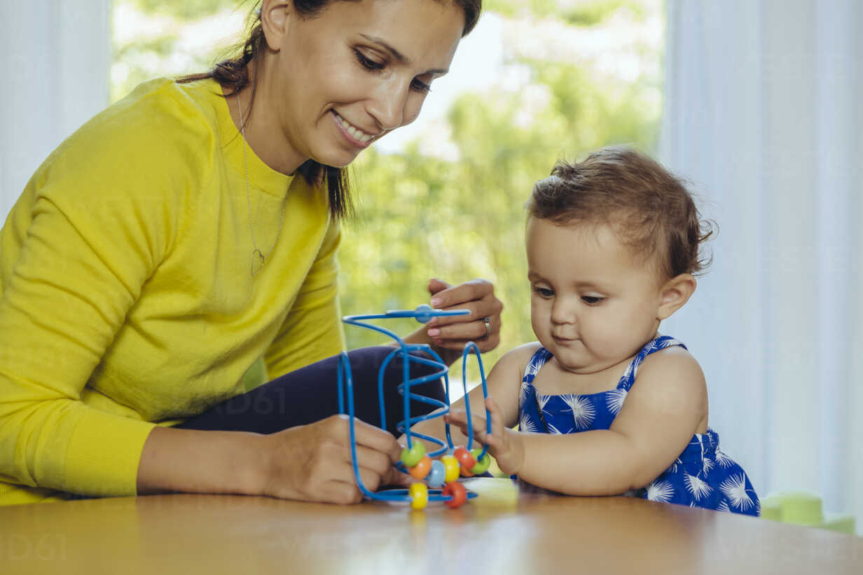 Happy mother and baby daughter playing with motoric loop - MFF04679 - Mareen Fischinger/Westend61