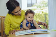 Mother and baby daughter looking at children's book - MFF04682