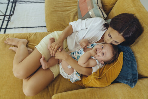 Mother cuddling and kissing her baby girl on couch - MFF04694