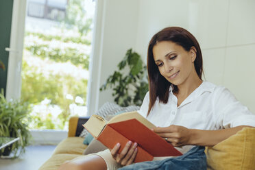 Smiling woman reading book on couch - MFF04697