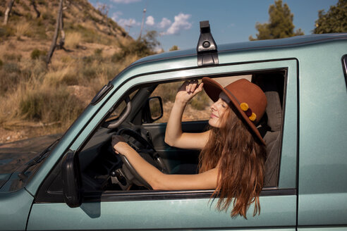 Smiling young woman wearing a hat sitting in a car - AFVF01560