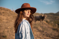 Portrait of young woman wearing a hat in rural landscape - AFVF01569