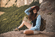 Smiling young woman on a hiking trip wearing a hat sitting on a rock - AFVF01581