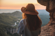 Rear view of woman on a hiking trip looking at view at sunset - AFVF01587