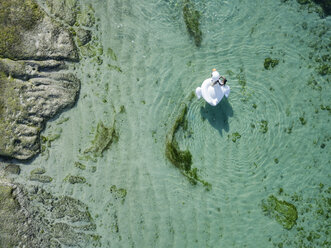 Indonesia, Bali, Aerial view of Karma Kandara beach, one woman, airbed floating on water - KNTF01669