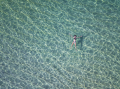Indonesia, Bali, Melasti, Aerial view of Karma Kandara beach, woman floating on water - KNTF01684
