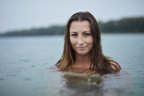 Portrait of freckled young woman  bathing in lake on rainy day - PNEF00882