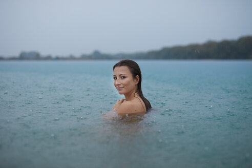 Portrait of smiling young woman  bathing in lake on rainy day - PNEF00891