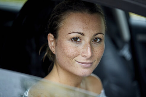 Portrait of freckled young woman looking out of car window - PNEF00897