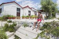 Boy sitting in swimming trunks in sunshine in front of a house - AZOF00045