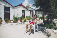 Portrait of a boy sitting in swimming trunks in sunshine in front of a house - AZOF00048