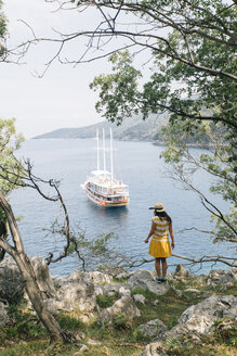 Croatia, Cres, woman standing at the coast looking at the sea with sailing ship - JES00152