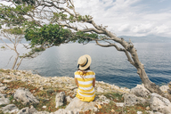 Croatia, Cres, woman sitting at the coast looking at the sea - JES00158