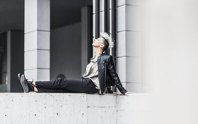 Punk woman sitting on a wall with closed eyes - GIOF04418