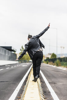 Rear view of punk woman balancing on a barrier at the roadside with outstretched arms - GIOF04430
