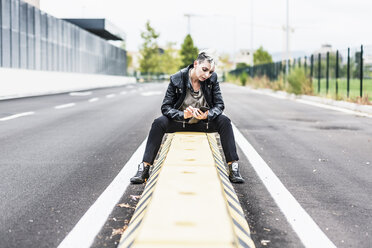 Punk woman sitting at the roadside using cell phone - GIOF04433