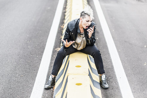 Aggressive punk woman sitting at the roadside screaming into cell phone - GIOF04436