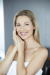 Portrait of smiling blond woman  wrapped in towel - PNEF00909