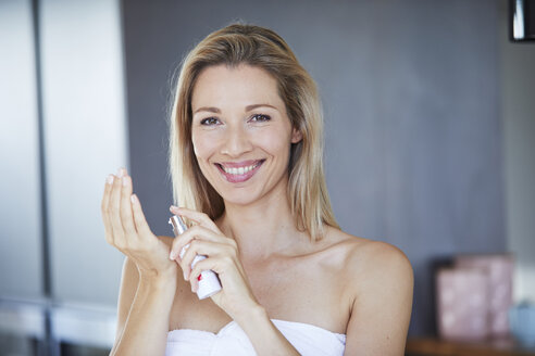 Portrait of smiling blond woman  with dispender applying face cream - PNEF00912