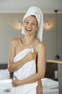 Portrait of laughing woman wrapped in towel standing in bedroom - PNEF00921