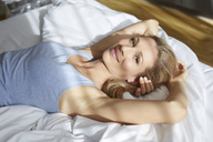 Portrait of smiling blond woman lying in bed in the morning - PNEF00930