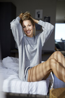 Portrait of smiling blond woman sitting on bed in the morning - PNEF00933