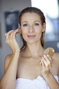 Portrait of blond woman applying makeup in the morning - PNEF00942