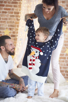 Boy trying on oversized Christmas Sweater with parents in bed - ABIF01037