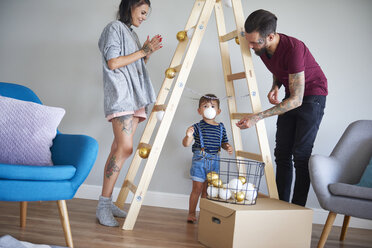 Modern family decorating the home at Christmas time using ladder as Christmas tree - ABIF01055