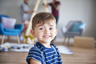 Portrait of smiling boy at home with parents in background - ABIF01058