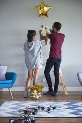 Modern couple decorating the home at Christmas time using ladder as Christmas tree - ABIF01064