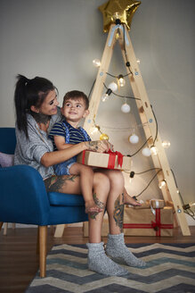 Happy boy opening Christmas present with his mother at home - ABIF01070
