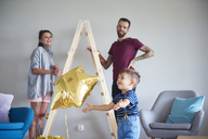 Modern family decorating the home at Christmas time using ladder as Christmas tree - ABIF01076