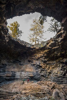 Mother and daughter inside lava tube, Grants, New Mexico, USA - AURF05472