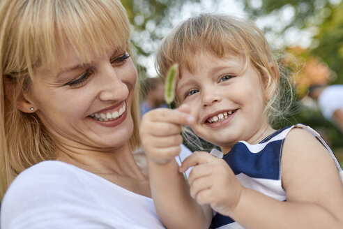 Happy mother with her daughter holding a stalk outdoors - ZEDF01552