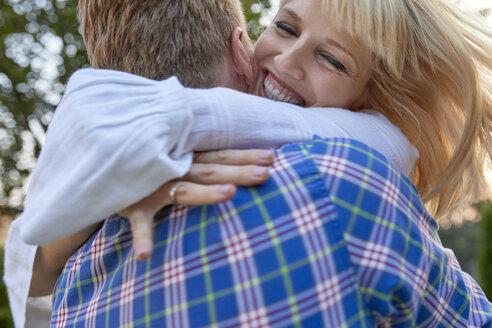 Happy couple hugging outdoors - ZEDF01561
