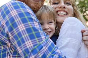 Happy parents hugging her daughter outdoors - ZEDF01564