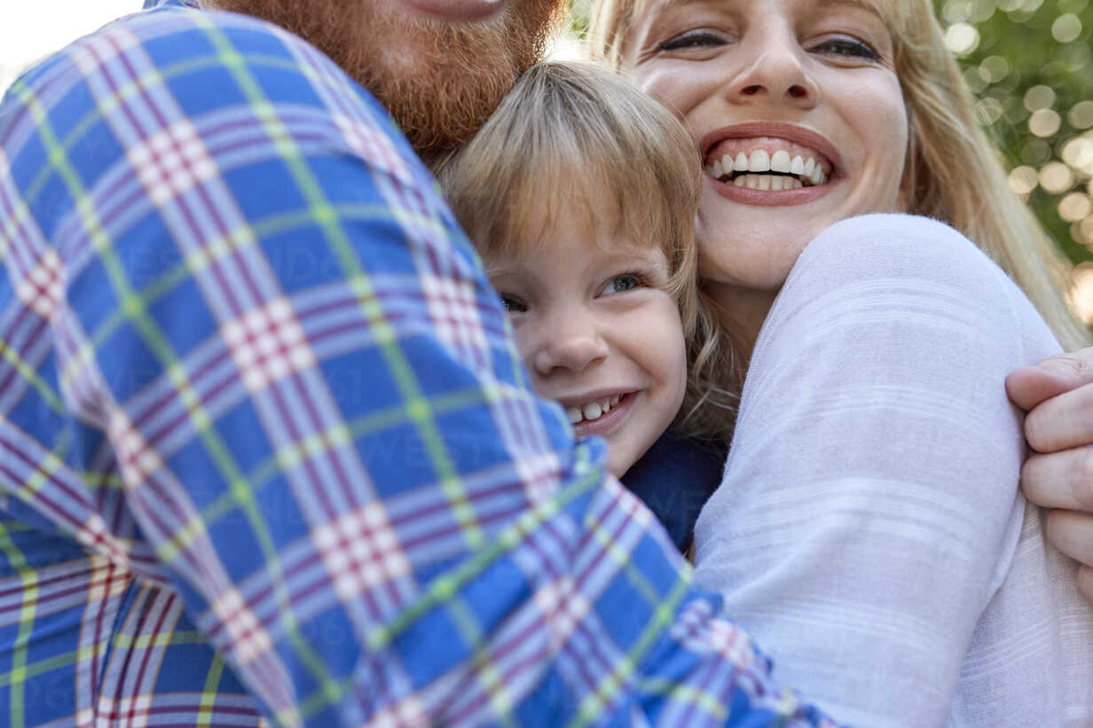 Happy parents hugging her daughter outdoors - ZEDF01564 - Zeljko Dangubic/Westend61
