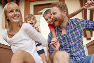 Happy family on porch of their home - ZEDF01570
