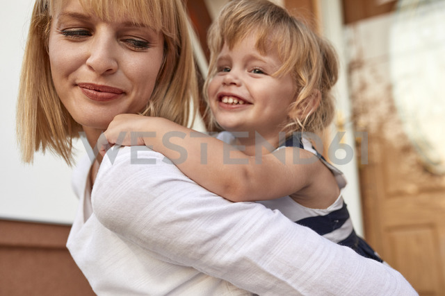 Smiling mother carrying her daughter piggyback in front of their house - ZEDF01573