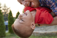 Happy playful father with his son in garden - ZEDF01579